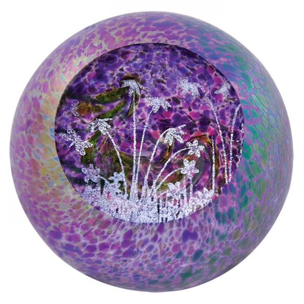 Purple iridescent speckled glass paperweight with interior of white flowers, grass and dragonflies