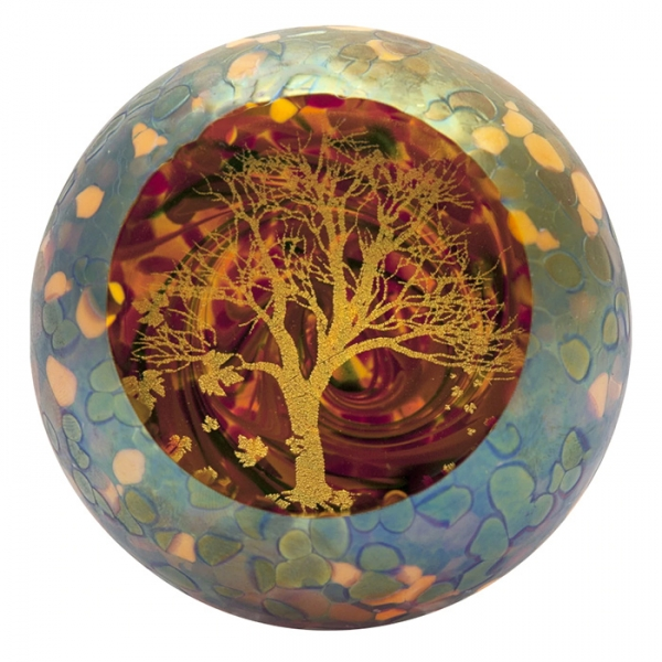 Gold and yellow speckled glass paperweight with interior of yellow tree