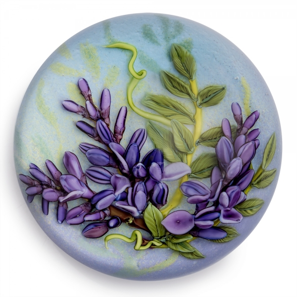 Glass round paperweight with realistic purple lilac flowers and green leaves with a light blue background