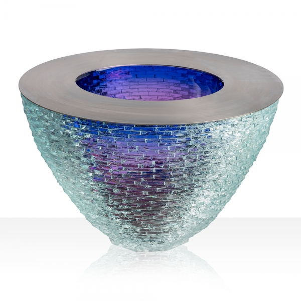 Fused glass bowl shaped sculpture with smooth purple center and jagged, staggered clear exterior. Metal piece on the top edge of the sculpture